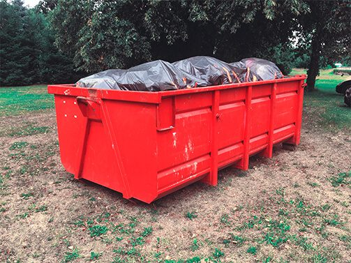 red dumpster filled with garbage bags