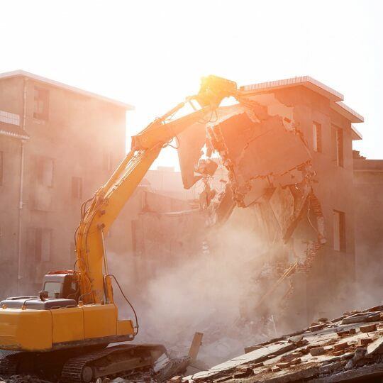 backhoe demolishing building