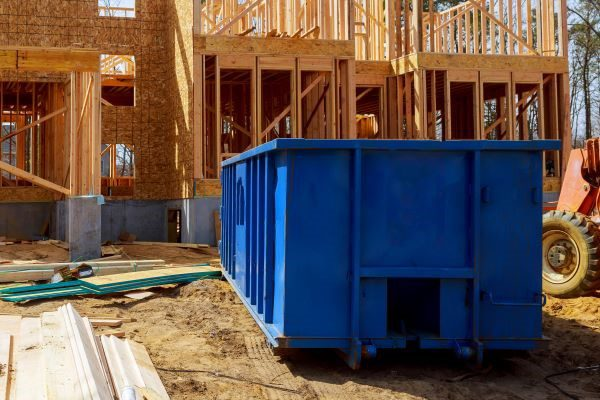 blue dumpster outside house being built