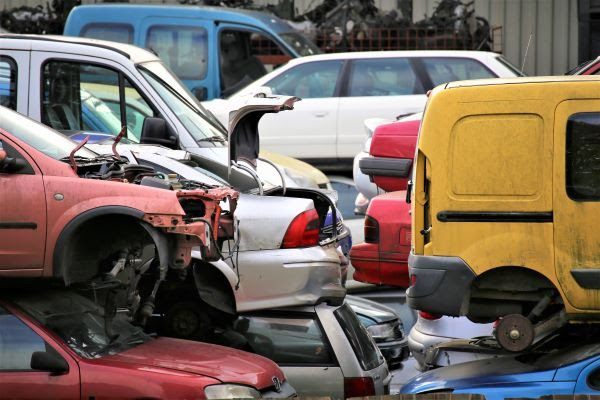 car salvage yard with cars being crushed