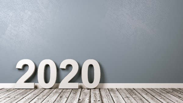 large 2020 numbers on a light gray wood floor in front of light blue wall