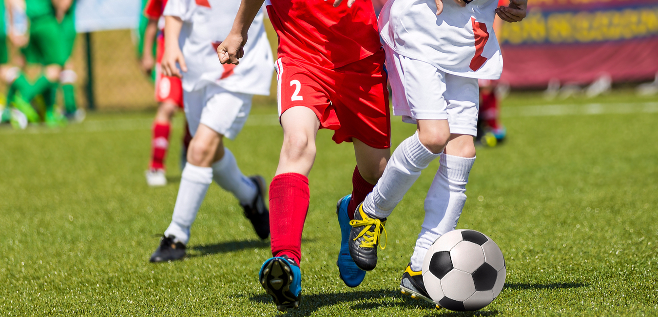 Soccer players in red and white uniforms on the field kicking soccer ball