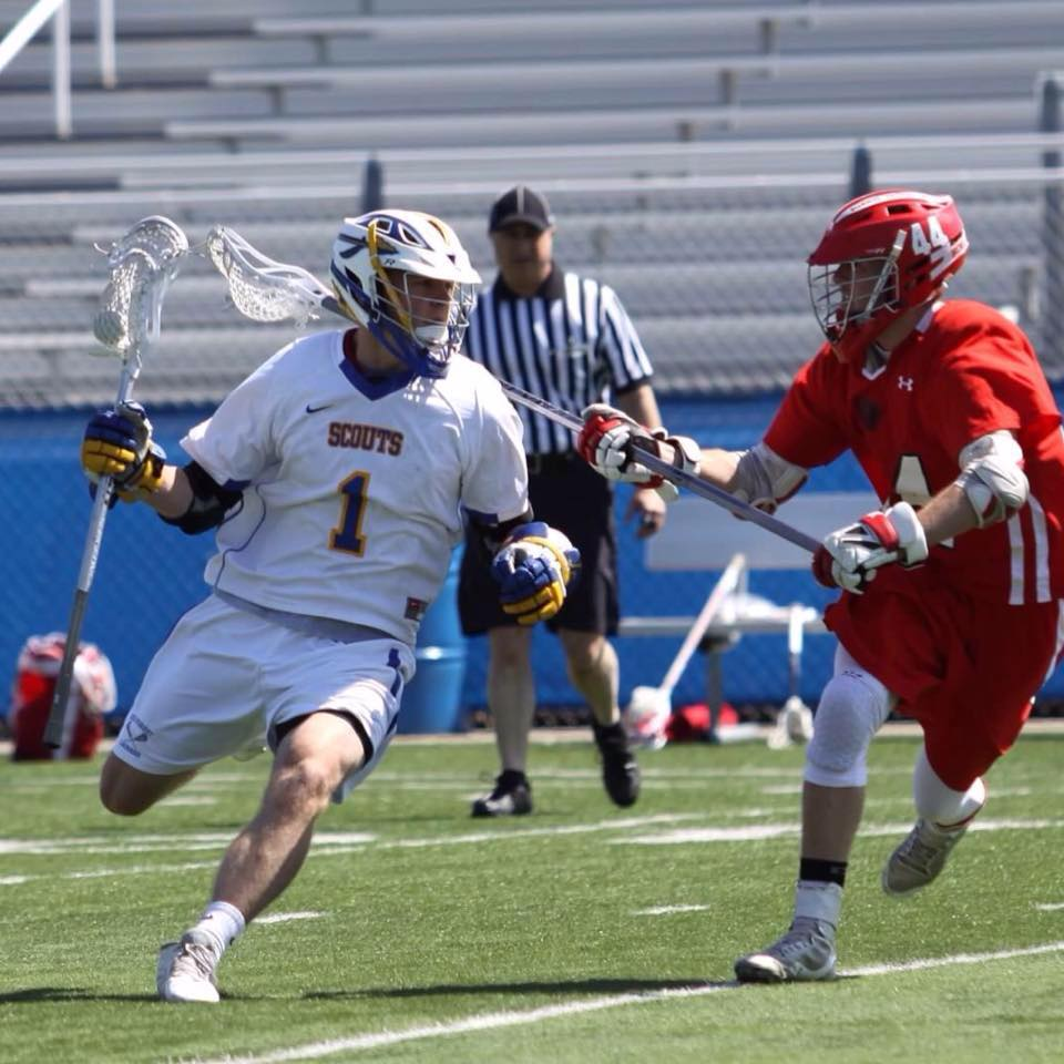 Two lacrosse players on opposing teams playing on field