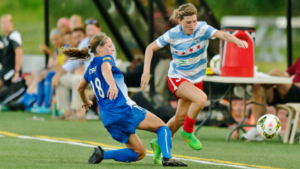 Two women's soccer players playing soccer match