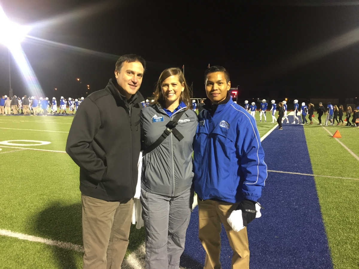 Dr. Chams standing with man and woman on football field at night