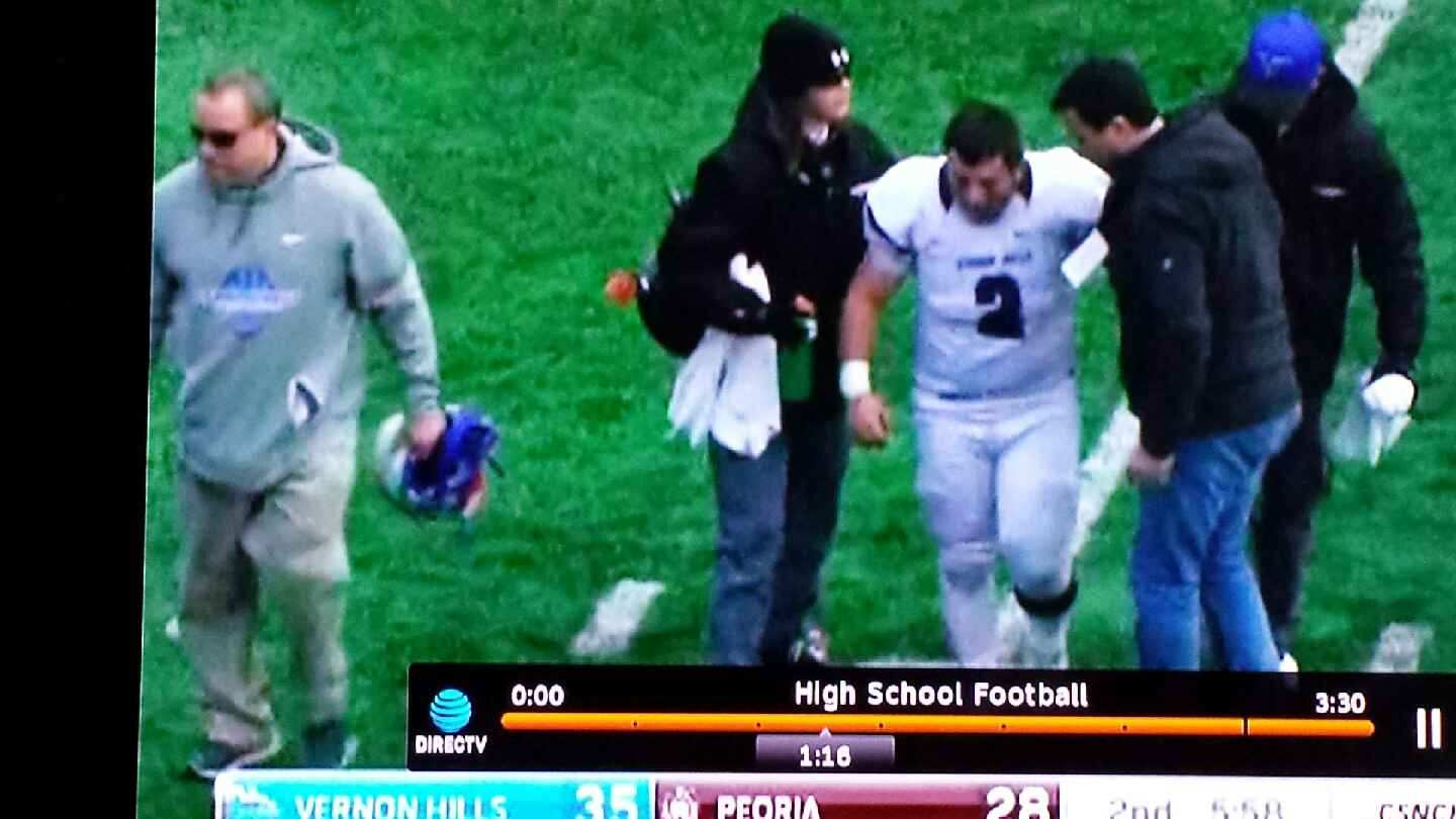 Football player walking off field after being injured