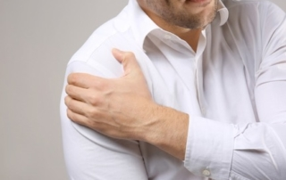 Man holding shoulder in pain.