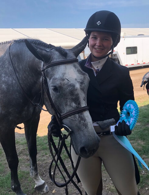 Girl smiling and posing with grey horse