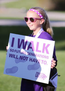 Girl in purple clothes outside holding sign