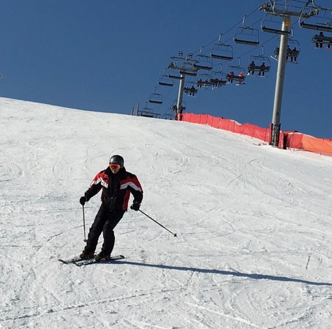 man in red and black jacket skiing down snow covered hill
