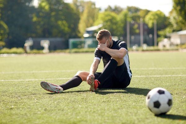 male soccer player sitting on field holding his injured foot
