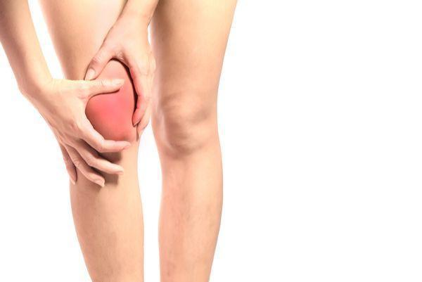 Women holding inflamed knee in pain