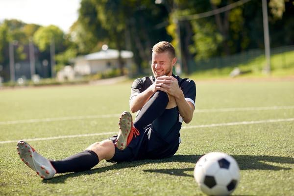 injured soccer player holding his knee on soccer field