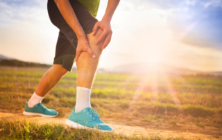 man holding his knee in pain while out for a run outside