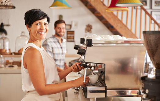 woman smiling while making a cup of coffee