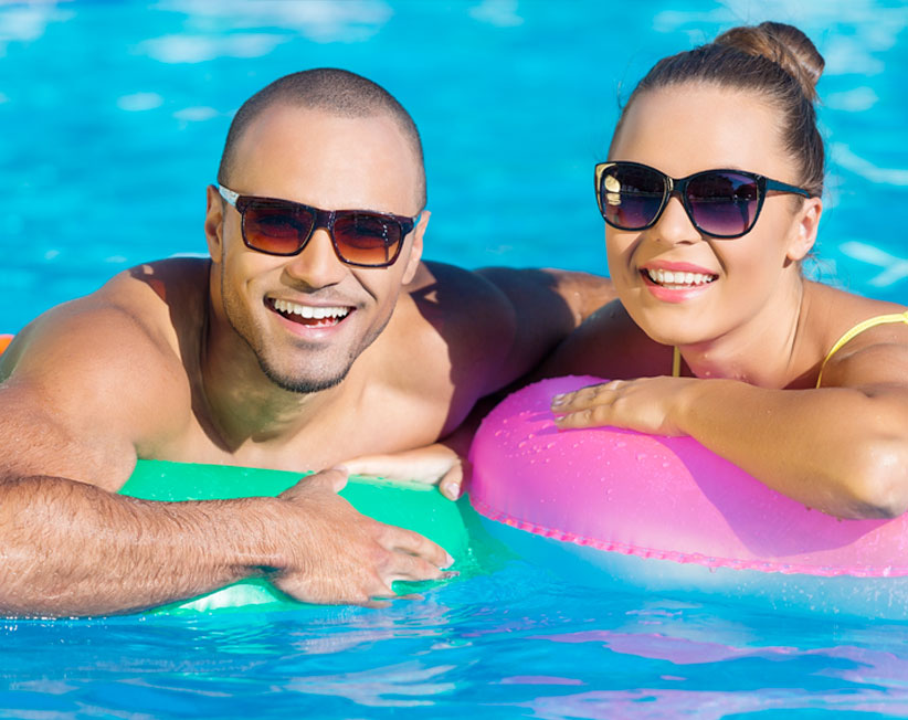 man and woman smiling in a pool and wearing sunglasses