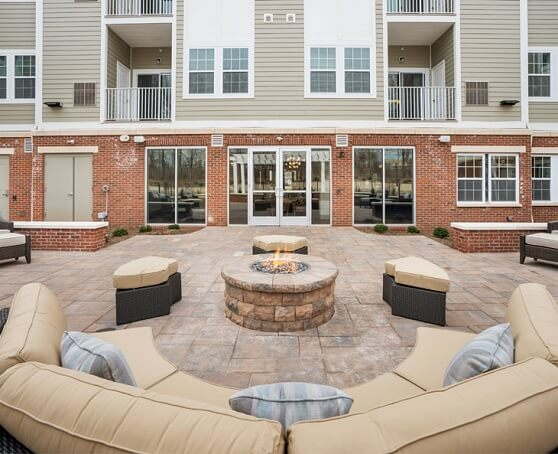 Outside apartment courtyard area with lit firepit and couches