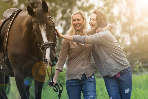 a mother and daughter petting a horse on a farm