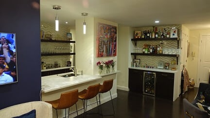 bar area with dark cabinetry and light counters