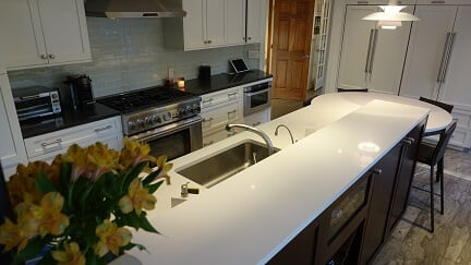 white cabinetry and large island with white counter tops