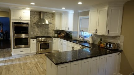 white kitchen cabinets with dark hardware and dark counter tops