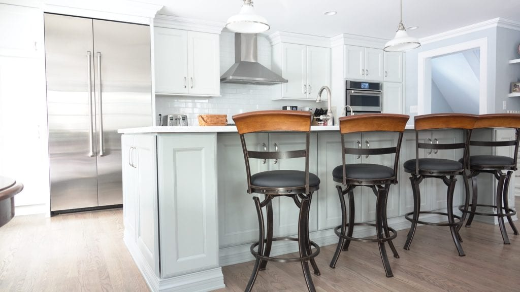 Updated white modern kitchen with hooded vent and sleek stainless steel appliances