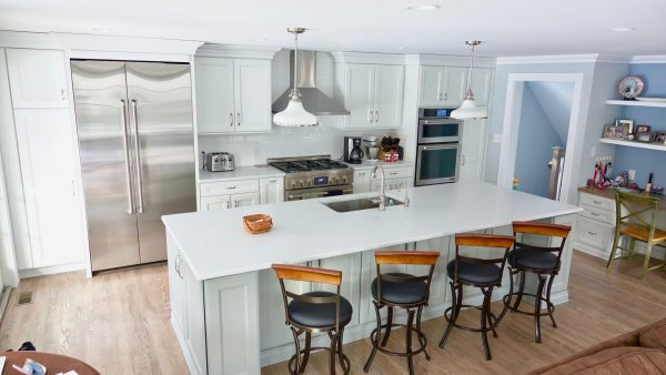 Upper angle of newly redone kitchen with high end appliances and hooded vent