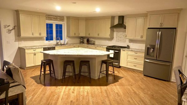 Updated modern kitchen with hooded vent and catty corner island with rustic bar stools