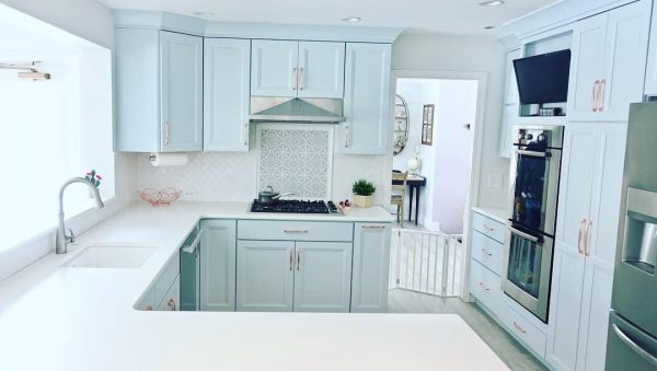Clean kitchen with dusty light blue cabinets and white countertops