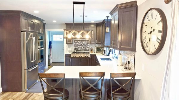 Image of a newly remodeled kitchen from behind peninsula barstool chairs