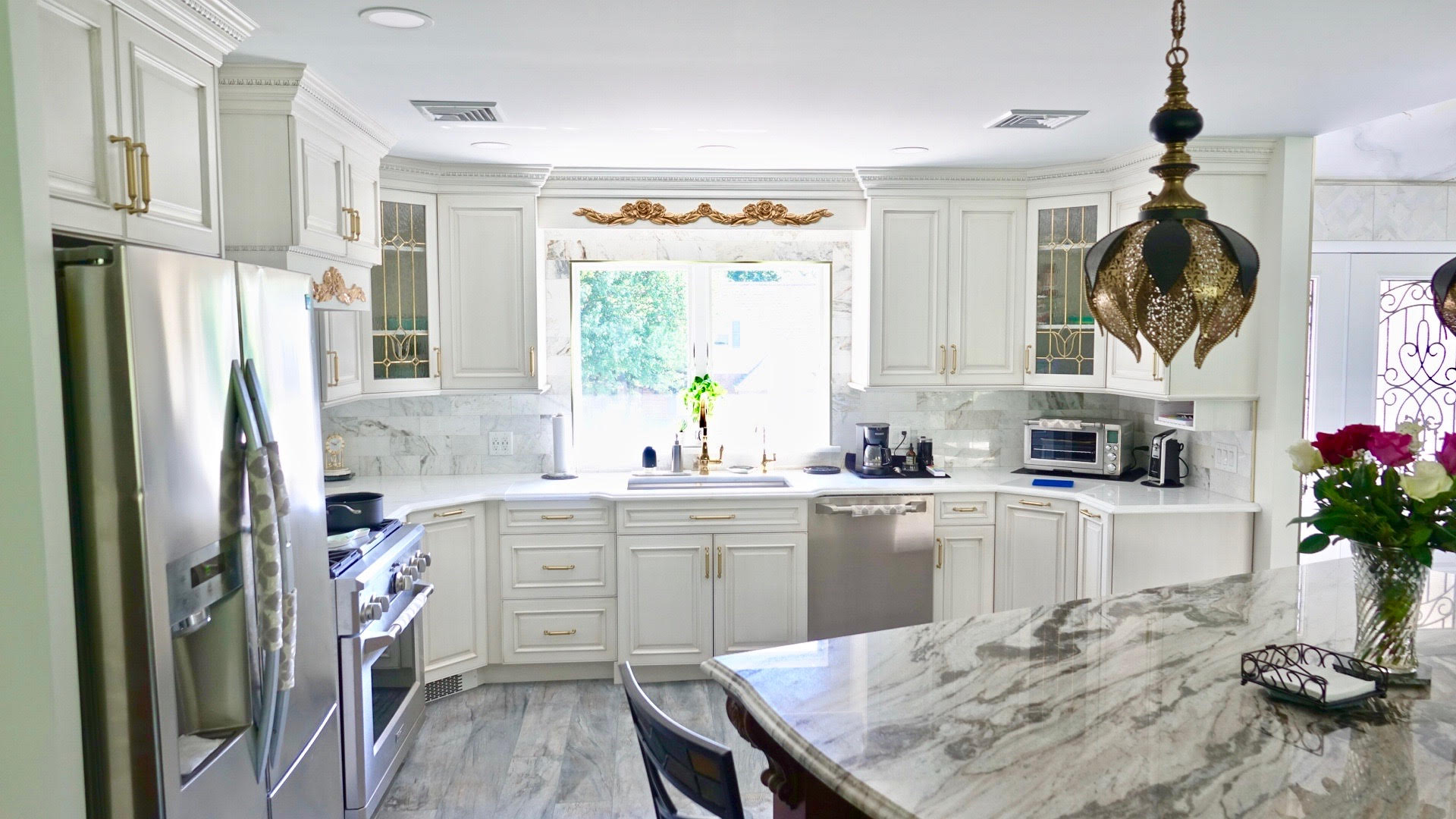 gray floors, white cabinets, gold hardware, and gold rose design over the kitchen sink
