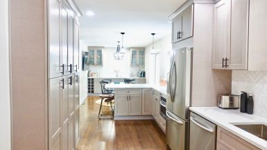 narrow white kitchen with many cabinets