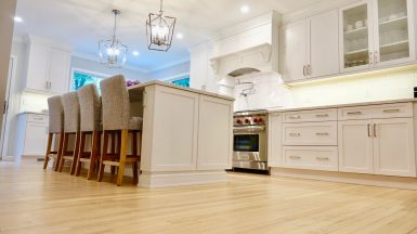 light brown floors with white cabinets and island
