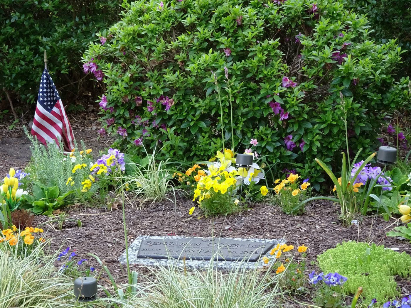 headstone surrounded by flowers and american flag