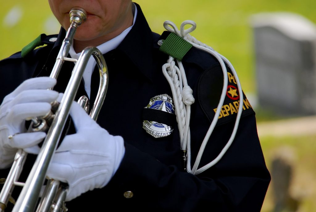 Police officer playing bugle at funeral