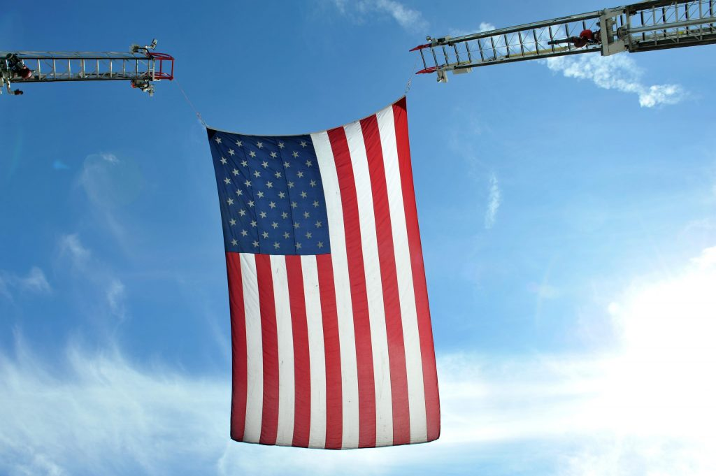 American flag held up by firetruck ladders
