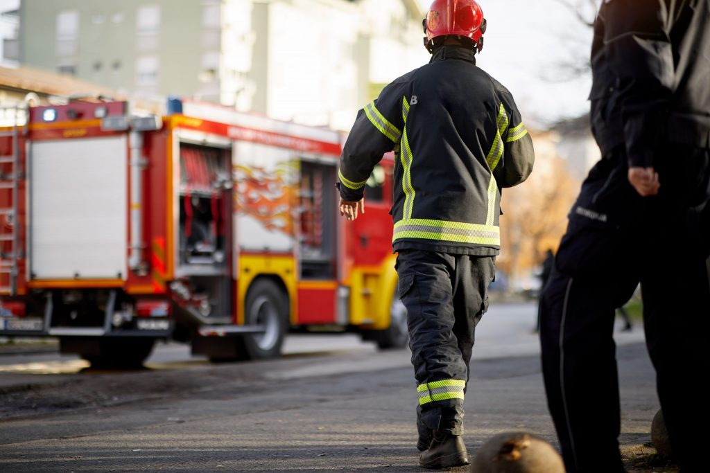 Fireman in uniform in front of fire truck going to rescue and protect.
