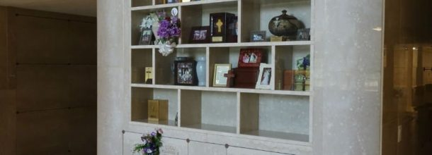 shelves in a mausoleum with flowers and ribbons from visitors