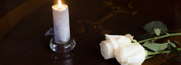 white candle next to white roses