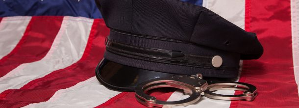 american flag with a police officer cap and hand cuffs