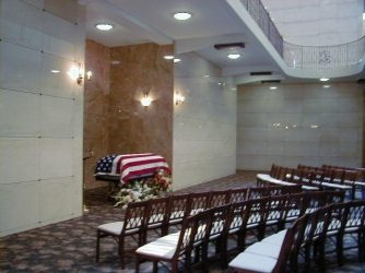 american flag drapped over the casket in a mausoleum
